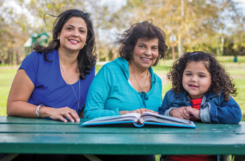 Mother, Daughter and Grandaughter reading a book smiling